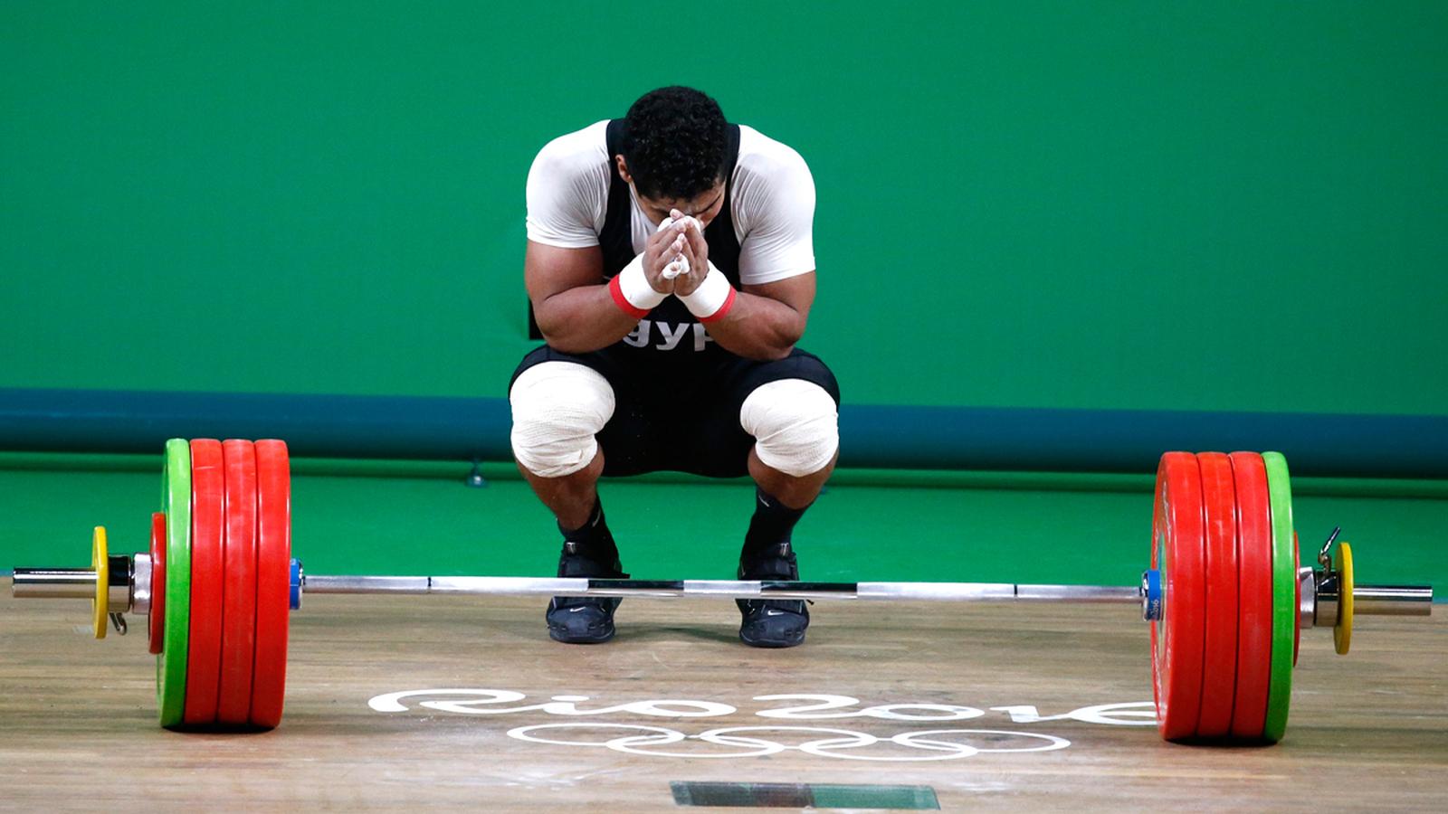 Египетский тяжелоатлет Мохаммед Махмуд совершает ритуал перед штангой
