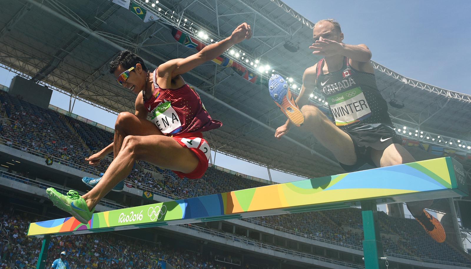 Легкоатлеты Хосэ Пенья из Венесуэлы и Крис Уинтер из Канады (справа) во время бега с препятствиямии