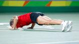 Бельгийская теннисистка Кирстен Флипкенс целует бразильский корт после выхода в следующий круг олимпийского турнира