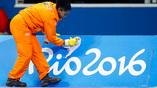 Служащая олимпийского бассейна прибирает территорию