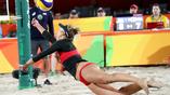 Американка Априль Росс на турнире по пляжному волейболу в полете за мячом