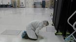 Микробиолог собирает пробы с пола простерилизованной комнаты