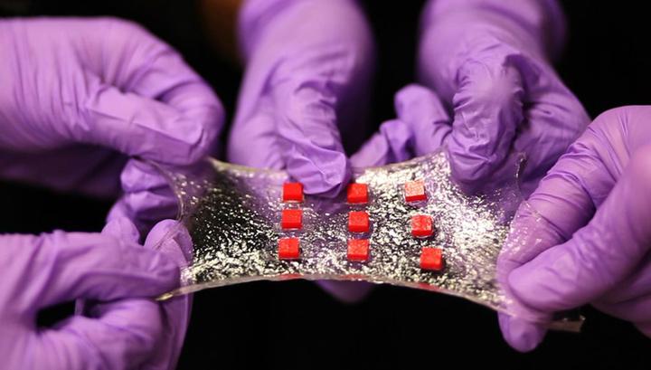 Гидрогелевый лист с полимерными вкраплениями (красные), которые могут включать электронные компоненты, например, температурные датчики, светодиоды и полупроводниковые микросхемы