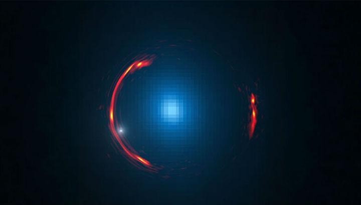 Составное изображение гравитационной линзы SDP.81 показывает искаженное изображение более далёкой галактики (красные дуги) и ближней галактики-линзы (синий объект в центре). Тёмная карликовая галактика обозначена белой точкой
