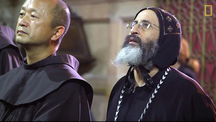 Монах-францисканец и коптский священник наблюдают за работой реставраторов в храме Гроба Господня. Кадр из видео National Geographic / Youtube