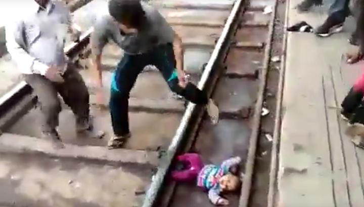 Чудом осталась в живых: маленькую девочку уронили под движущийся поезд. Видео