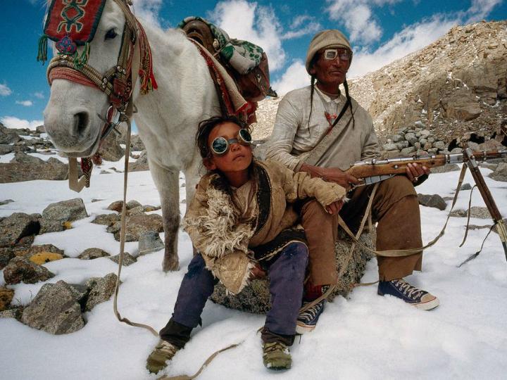 Отец и сын, жители Тибета, поднимаются на гору Кайлас