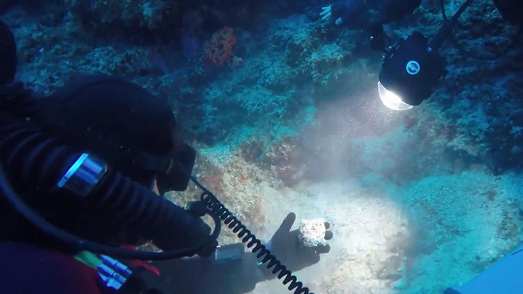 Брендан Фоули показывает коллегам бронзовый артефакт, похожий на деталь Антикитерского механизма. Кадр из видео 2017 Return to Antikythera Expedition