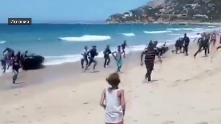Испания: к пляжу с десятками загорающих причалила лодка с десятками мигрантов