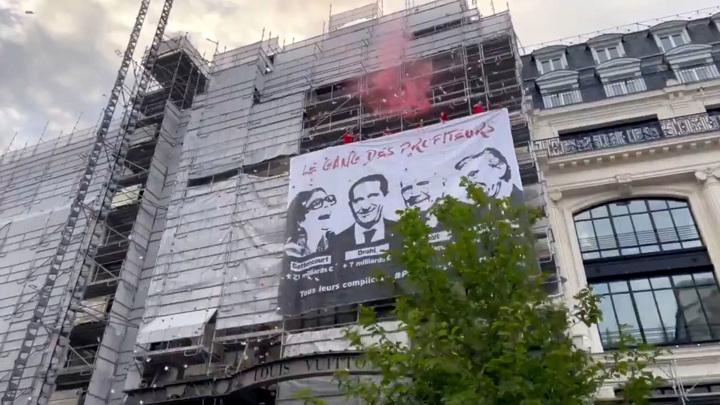 В Париже активисты закрасили витрины универмага и повесили баннер