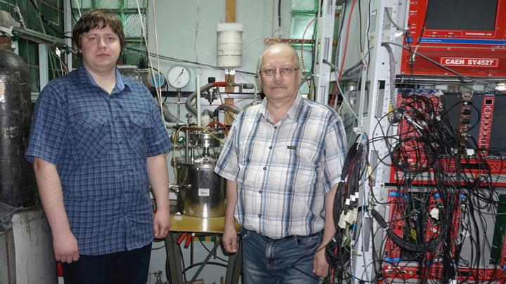 Егор Фролов и Алексей Бузулуцков возле прототипа двухфазного детектора, разработанного в ИЯФ СО РАН.